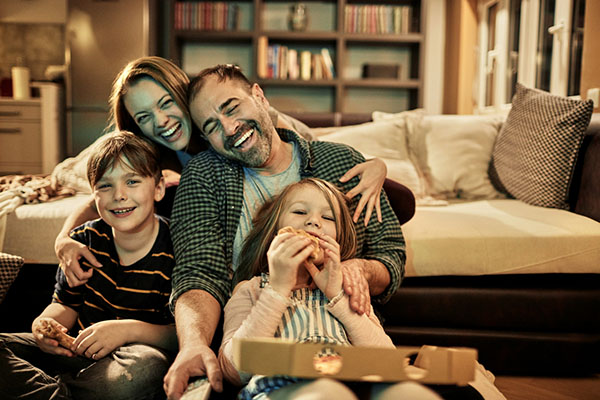 happy family watching a movie together and eating pizza