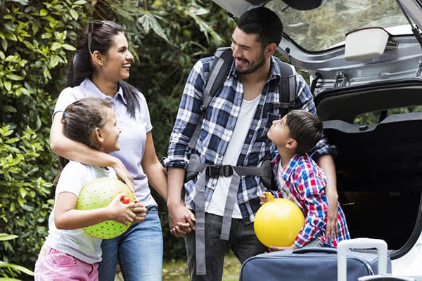 a family packs their car for vacation